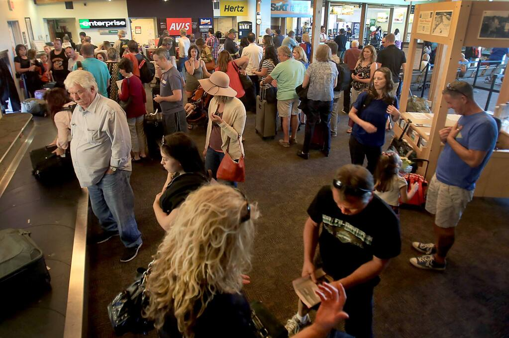After an Allegiant Air flight deplaned, the terminal at the Charles M. Schulz Sonoma County Airport is jammed with passengers waiting for luggage and those in line for rental cars, Thursday Sept. 15, 2016 in Santa Rosa. (Kent Porter / The Press Democrat) 2016