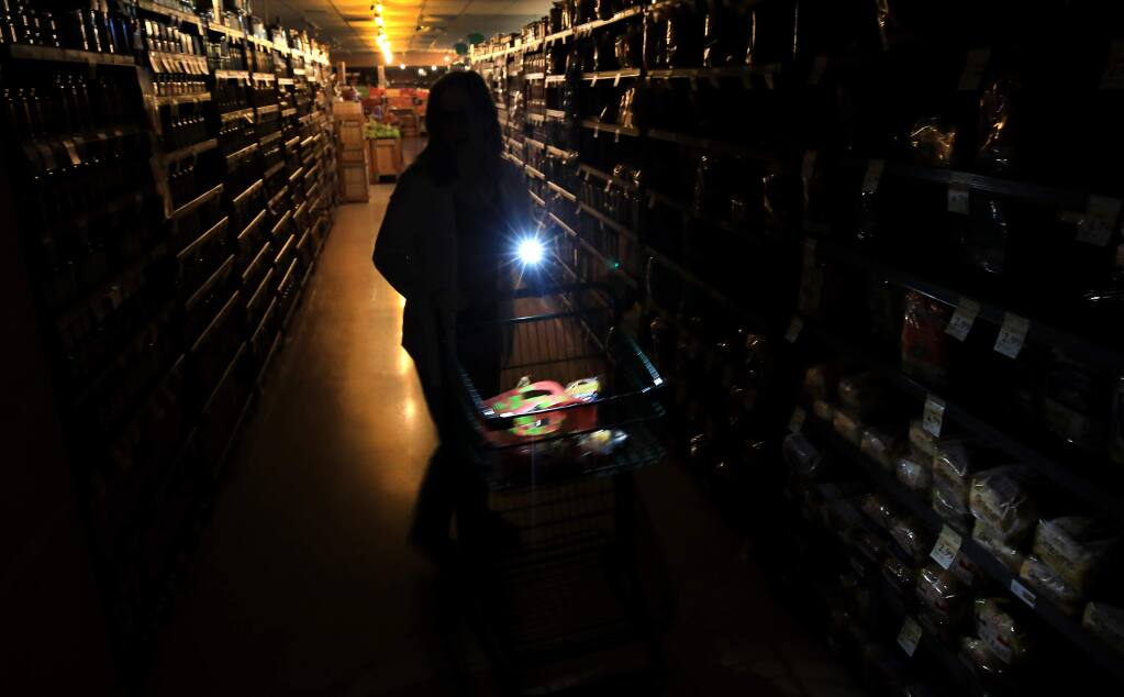 Suzanne Allen shops in a darkened Oliver's Supermarket in Rincon Valley, Wednesday, Oct. 23, 2019. The west side of the store was lit by patio lights powered by a generator as power was shut off again by PG&E due to fire danger. (KENT PORTER/ PD)