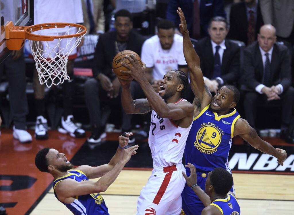 Toronto Raptors forward Kawhi Leonard (2) knocks down Golden State Warriors guard Stephen Curry, left, as he drives to the net past Golden State Warriors guard Andre Iguodala (9) during the first half of Game 1 of basketball's NBA Finals, Thursday, May 30, 2019, in Toronto. (Nathan Denette/The Canadian Press via AP)