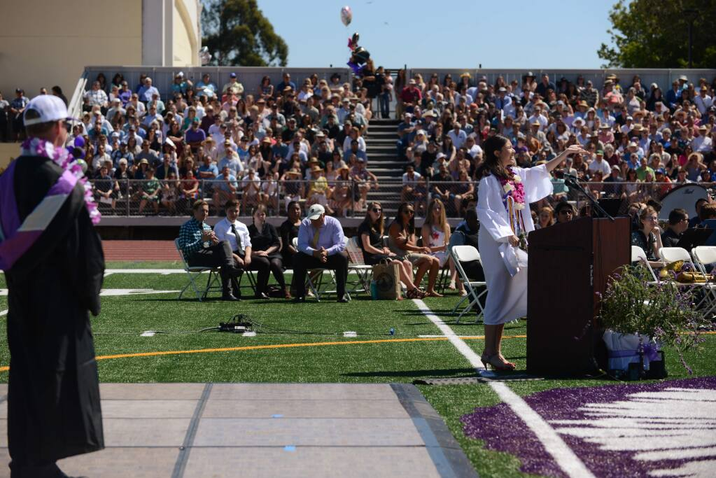 Petaluma High School Principal David Stirrat, left, watches Lulabel Seitz, right, gesturing for crowd support which she loudly received after her microphone was shut off by school officials during her valedictorian speech at the Petaluma High School Graduation ceremony held Saturday in Petaluma, California. June 2, 2018.(Photo: Erik Castro/for The Press Democrat)