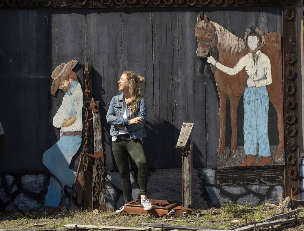Shawna DeGrange, owner of the Cloverleaf Ranch, stands with cutouts painted by her uncle on one of the few buildings left after the Tubbs Fire in 2017. (Photo by John Burgess/The Press Democrat)
