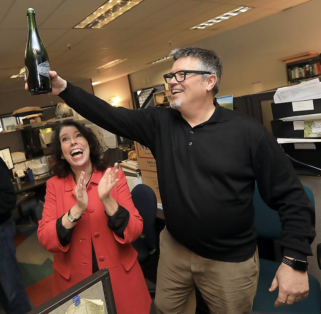 Press Democrat executive editor Catherine Barnett, left, and managing editor Ted Appel celebrate with colleagues and sparkling wine in the Press Democrat newsroom on April 16, 2018, after the newsroom learned it had been awarded the Pulitzer Prize for its coverage of the 2017 wildfires. (Kent Porter / Press Democrat)
