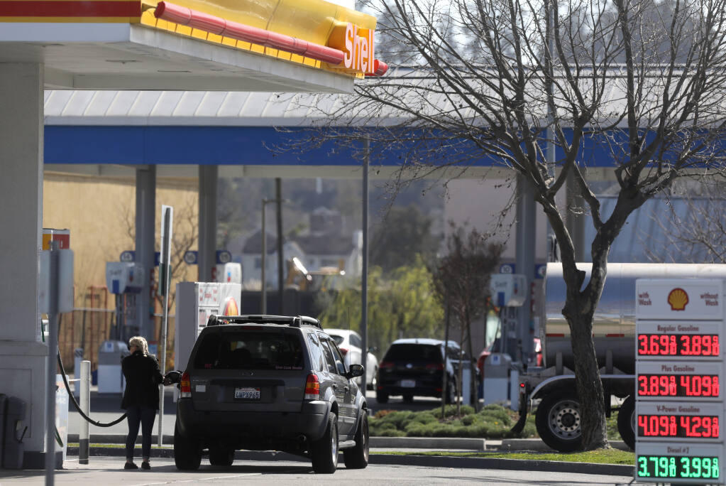 A woman fills her vehicle with gas at the Shell station located across the street from a Chevron gas station at Lakeville Street and Caulfield Lane in Petaluma on Thursday, March 4, 2021. The Petaluma City Council on March 1 voted to ban new gas station construction, and other agencies are now exploring the same step. (BETH SCHLANKER/THE PRESS DEMOCRAT)