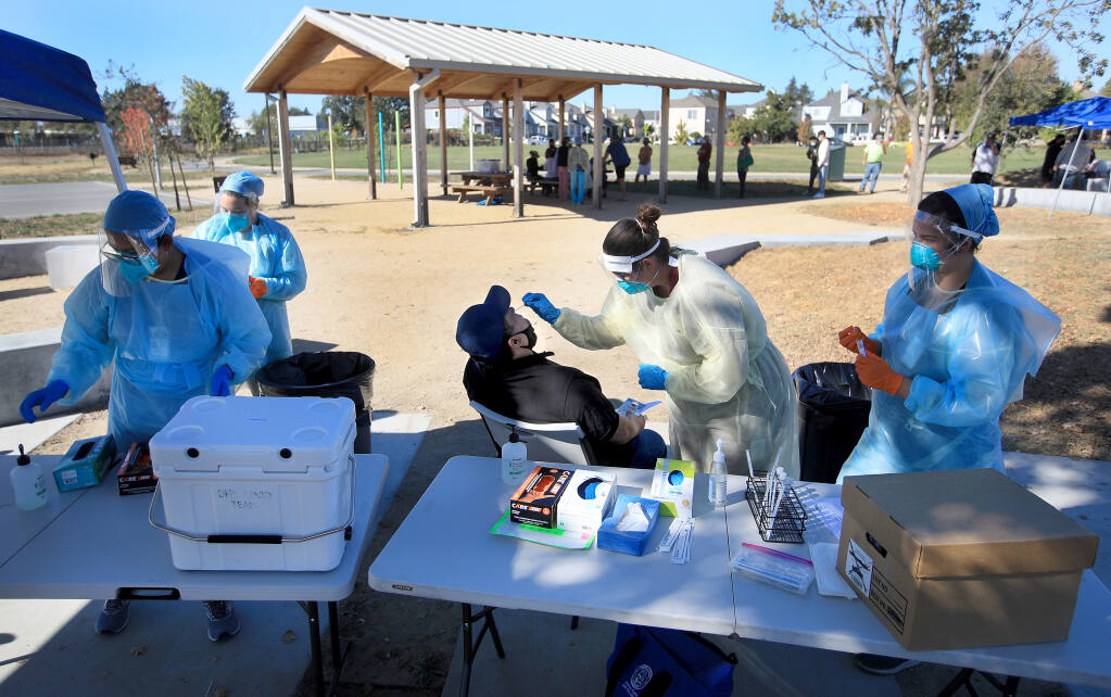 Sergio Guzman of Santa Rosa receives a COVID-19 nose swab from Sonoma County Public Health nurse Devin Andrews as Nicole Callopy assists, Tuesday, Oct. 20, 2020, at Andy's Unity Park in Santa Rosa. At left are Adriana Andres and Ellen Armour. (Kent Porter / The Press Democrat) 2020