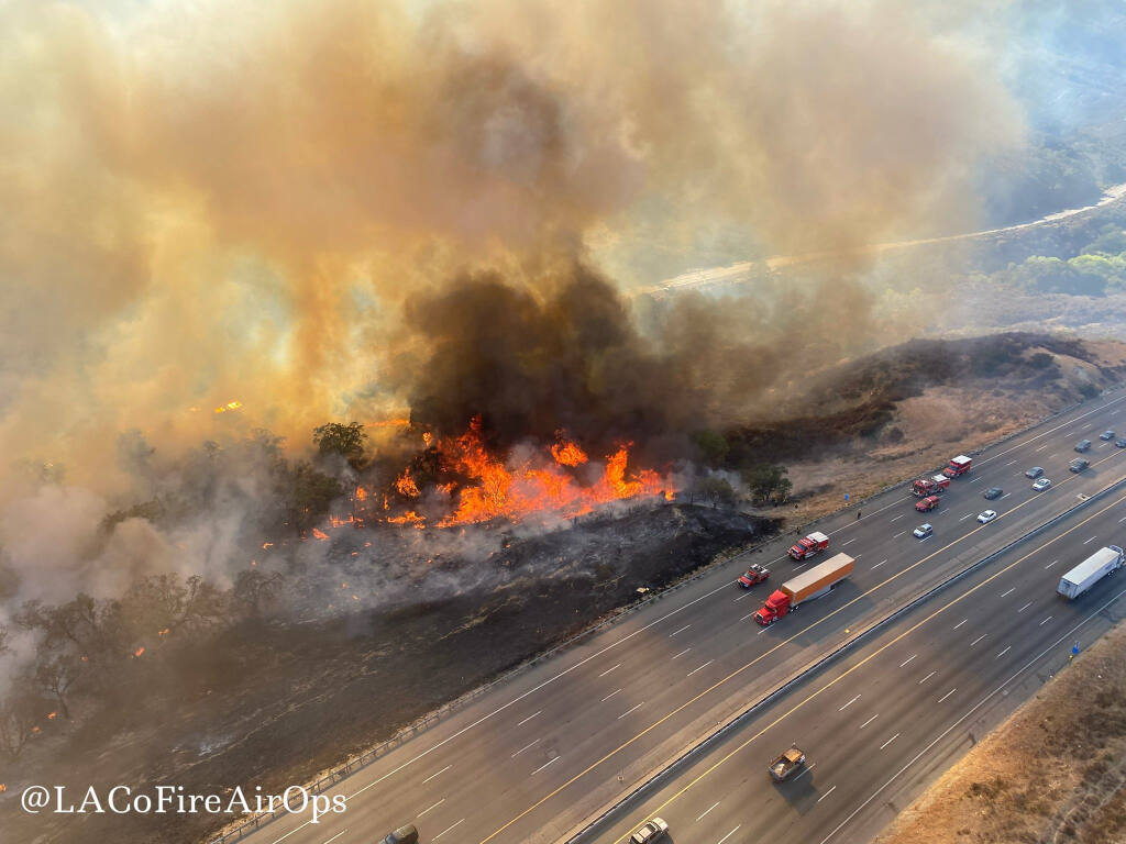 In this aerial photo released by the Los Angeles County Fire Department Air Operations traffic passes the Route fire, a brush wildfire off Interstate 5 north of Castaic, Calif., on Saturday, Sept. 11, 2021.  (Los Angeles County Fire Air Operations via AP)