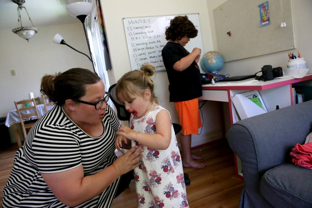 Rachael Hairston Loveridge reacts to the fresh nail polish on the fingertips of her daughter, Helen Loveridge, 2, while her son, Kayden Loveridge, 9, stands at his school desk in their apartment in Sonoma on Monday, July 13, 2020. (Beth Schlanker / The Press Democrat)