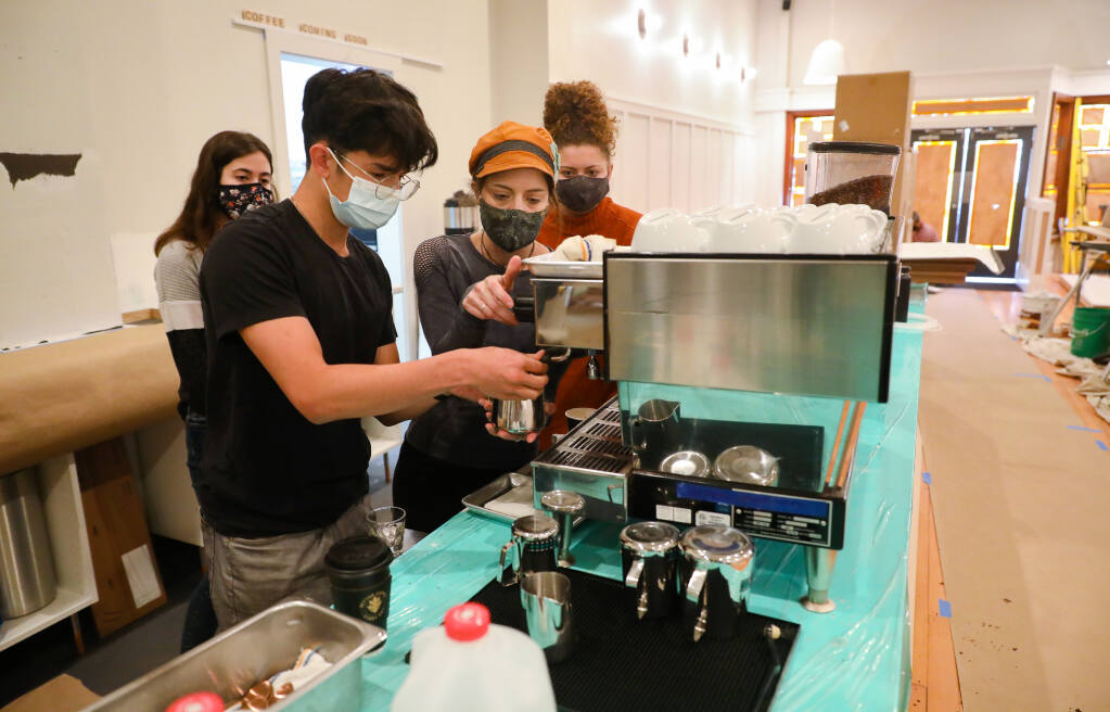 Lead barista Shelby Kobelin, second from right, shows trainee Alexander Limper how to operate the espresso machine at Black Oak Coffee Roasters, as trainees Jenna Burris, left, and Alex Shoop look on, in Healdsburg on Friday, April 9, 2021.  (Christopher Chung/ The Press Democrat)