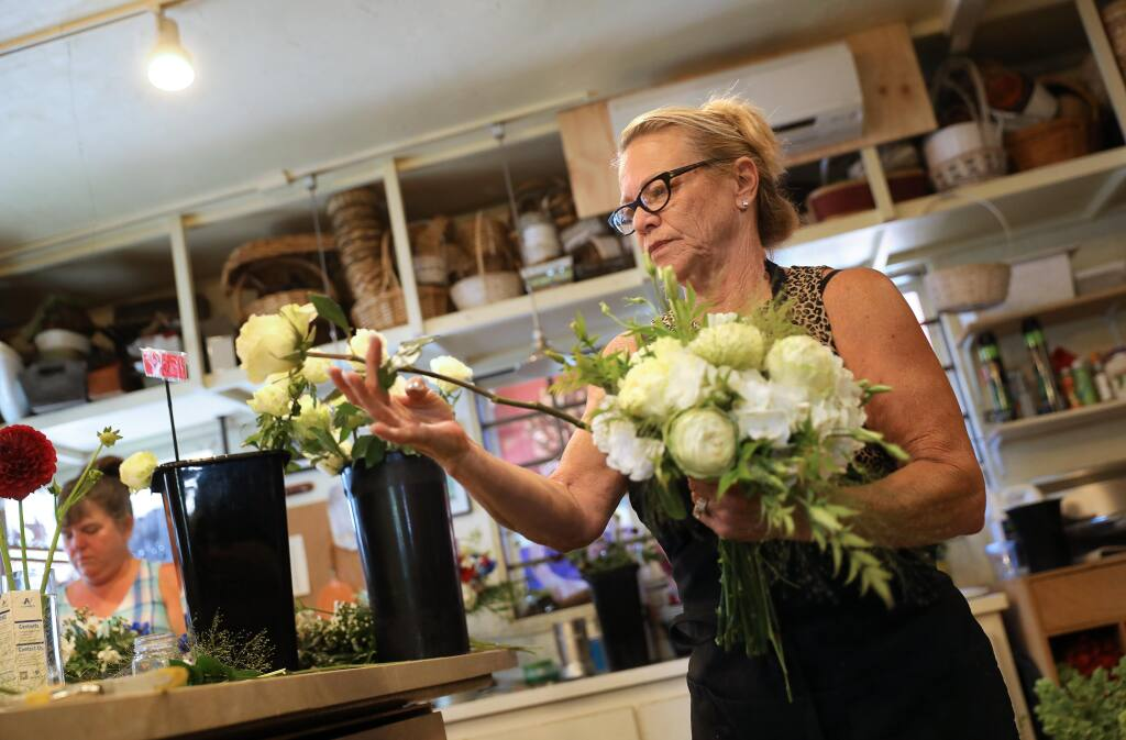 Pedy Lawson, owner of Pedy's Petals, puts together a bridal bouquet for an upcoming wedding elopement ceremony in Santa Rosa on Wednesday, July 1, 2020.  (Christopher Chung/The Press Democrat)