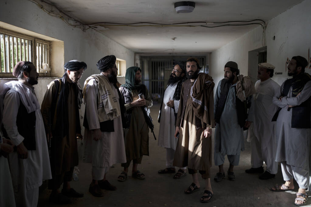 Taliban fighters, some former prisoners, chat in an empty area of the Pul-e-Charkhi prison in Kabul, Afghanistan, Monday, Sept. 13, 2021. Pul-e-Charkhi was previously the main government prison for holding captured Taliban and was long notorious for abuses, poor conditions and severe overcrowding with thousands of prisoners. Now after their takeover of the country, the Taliban control it and are getting it back up and running, current holding around 60 people, mainly drug addicts and accused criminals. (AP Photo/Felipe Dana)