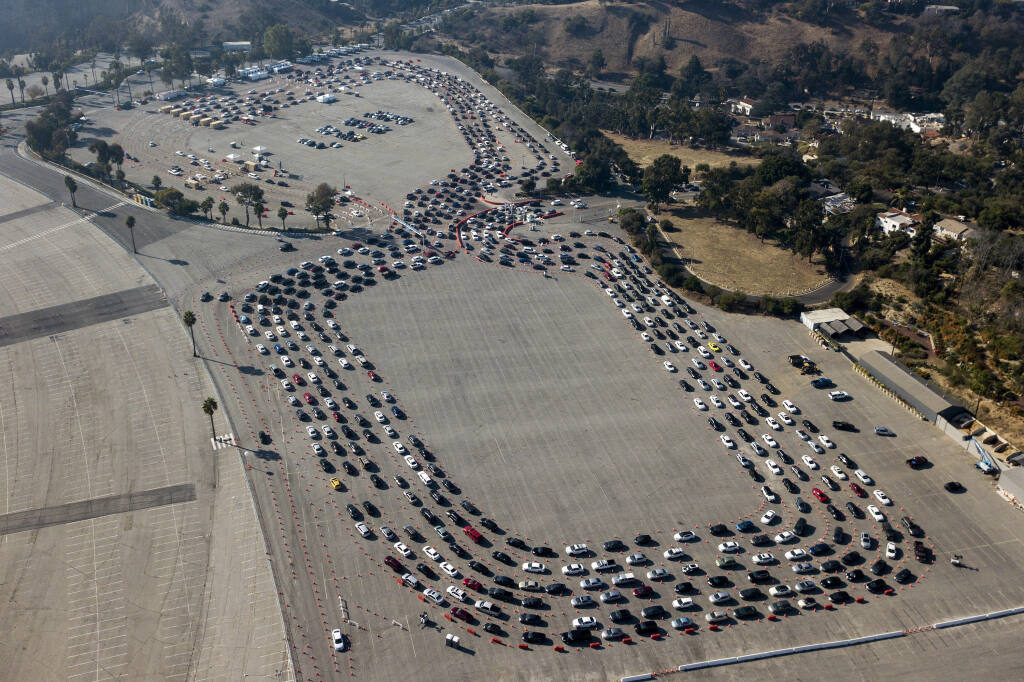Motorists queue up to take a coronavirus test in a parking lot at Dodger Stadium, Monday, Jan. 4, 2021, in Los Angeles. (AP Photo/Ringo H.W. Chiu)