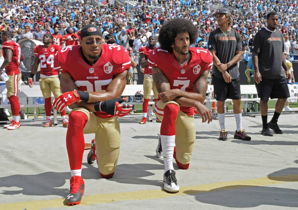 San Francisco 49ers' Colin Kaepernick (7) and Eric Reid (35) kneel during the national anthem before a game against the Carolina Panthers in Charlotte, N.C., Sunday, Sept. 18, 2016. (AP Photo/Mike McCarn)