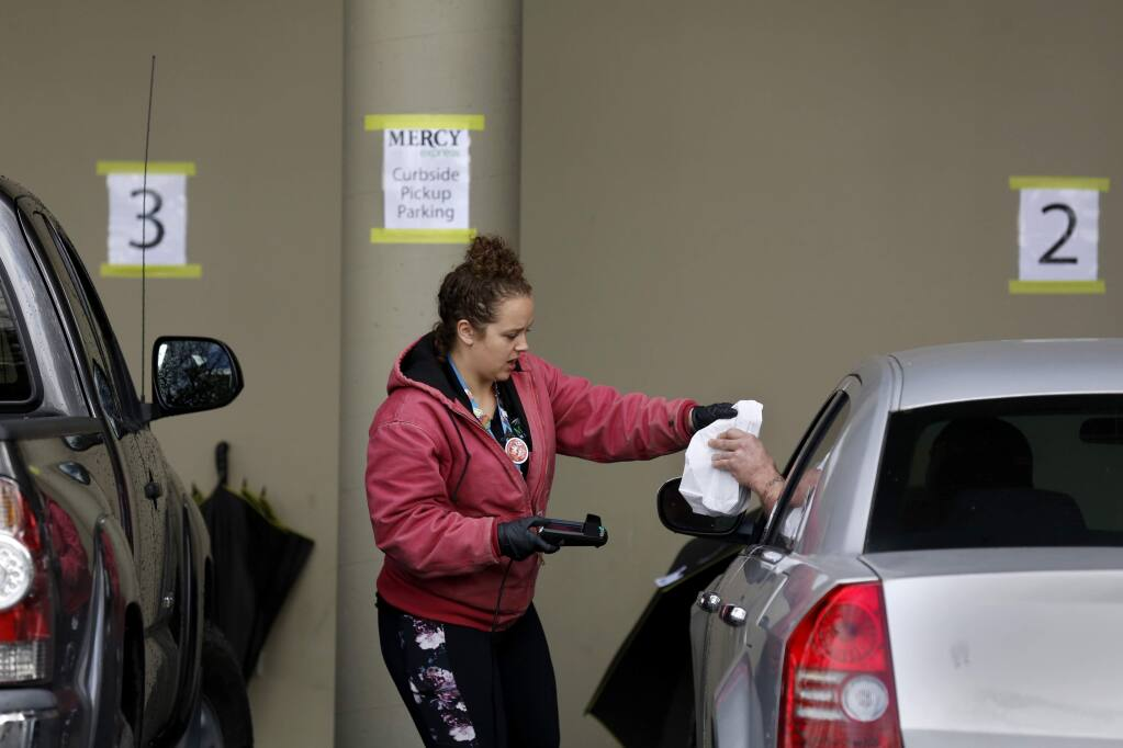 Employee Cari Garcia checks out a customer as part of the new curbside pickup at Mercy Wellness dispensary in Cotati on Tuesday, March 24, 2020. (BETH SCHLANKER/ The Press Democrat)