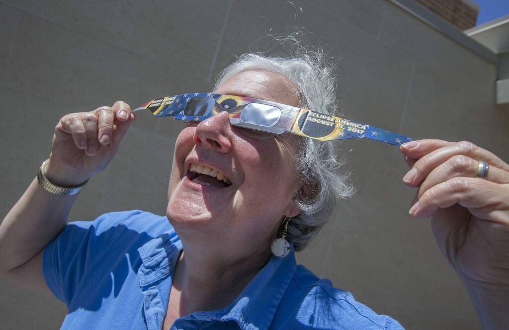 Children services librarian Clare O'Brien demonstrates a pair of the solar-eclipse-viewing glasses that were given away at the Sonoma Valley Regional Library in 2019 (Photo by Robbi Pengelly/Index-Tribune)