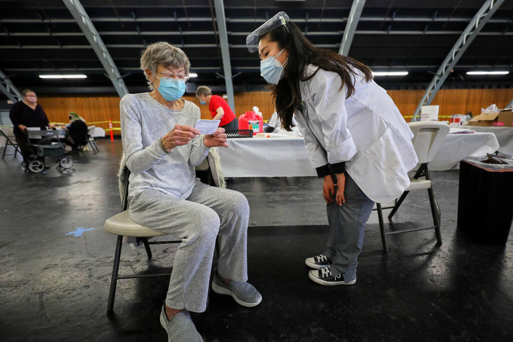 Betsy Todd, left, receives a card for her second coronavirus vaccine appointment after getting her first shot from Safeway pharmacy graduate intern Nancy Kong at a coronavirus vaccination site at the Sonoma County Fairgrounds in Santa Rosa on Wednesday, Feb. 3, 2021. (Christopher Chung / The Press Democrat)