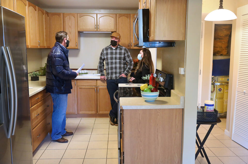 Realtor David Rendino, left, talks with Chris Palmer and Stephanie Reynolds as they conduct an inspection of the condominium they are in the process of buying in Santa Rosa on Monday, January 25, 2021.  (Christopher Chung/ The Press Democrat)