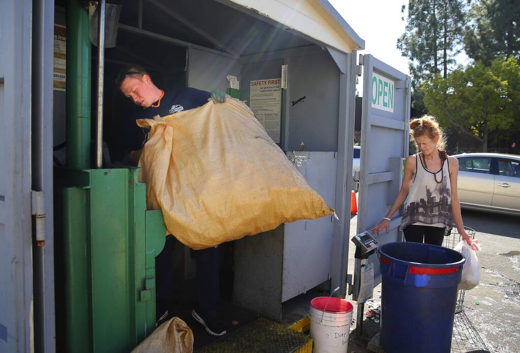 Joe Gali loads plastic bottles into a compactor while Betty Eppley waits for her receipt at the RePlanet recycling center in Rohnert Park, on Thursday, February 25, 2016. (Christopher Chung/ The Press Democrat)