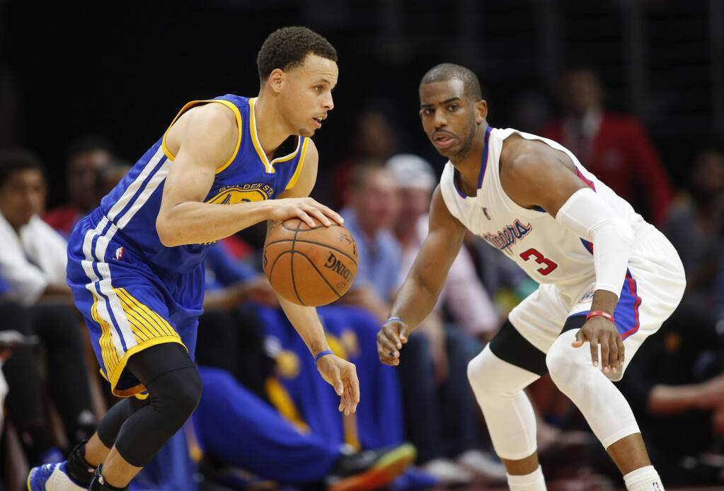 The Golden State Warriors' Stephen Curry, left, dribbles while the Los Angeles Clippers' Chris Paul, right, defends him during the first half Tuesday, March 31, 2015, in Los Angeles. (AP Photo/Danny Moloshok)