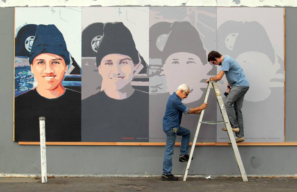 Local artist Mario Uribe, left, holds a ladder for assistant Daniel Doughty as they install a mural in honor of Andy Lopez titled 'Mindfulness.' The temporary mural was mounted friday morning on a condemned former gas station on West Ave. and Sebastopol Rd.