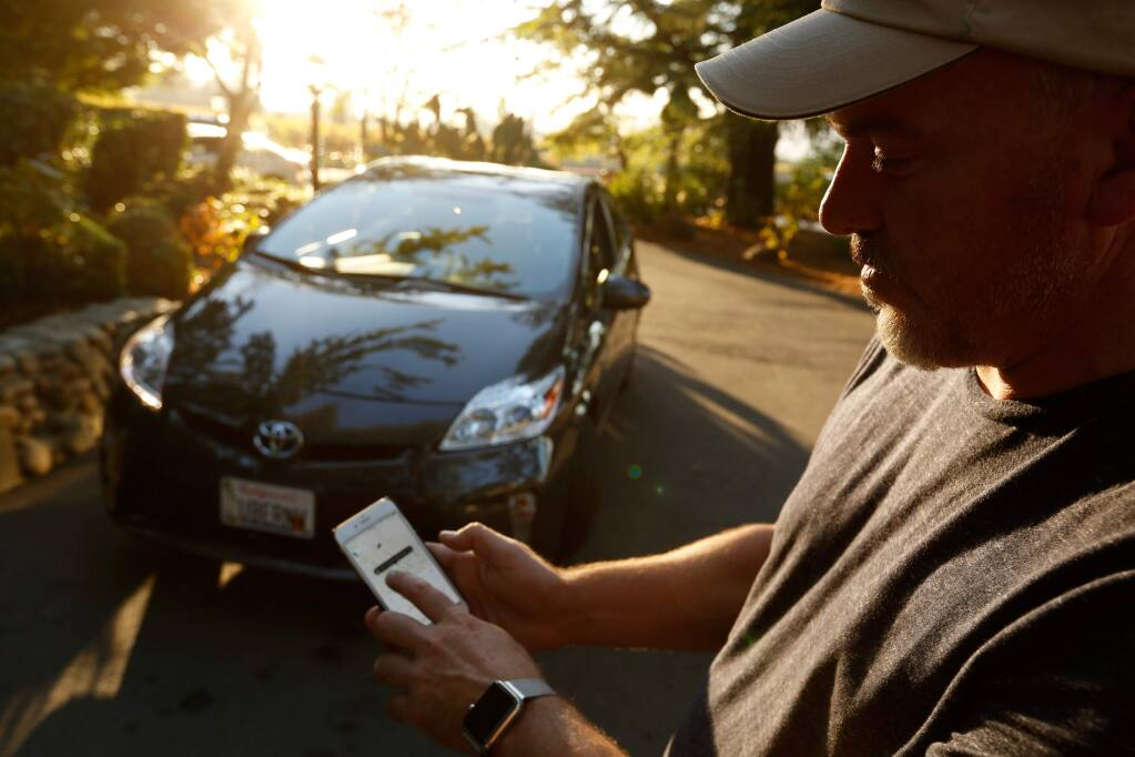 Uber driver Peter Stetson looks as the Uber passenger app in front of his car, in Napa, California on Saturday, November 7, 2015. (Alvin Jornada / The Press Democrat)