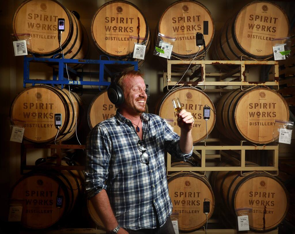 Spirit Works Distillery owner/distiller Timo Marshall samples whiskey that has been listening to Prince and Michael Jackson for three years through headphone attached to the bung. Employees created their own playlists to see whether whiskey tastes better listening to Led Zeppelin or if the control barrels in silence fared better. (John Burgess/The Press Democrat)