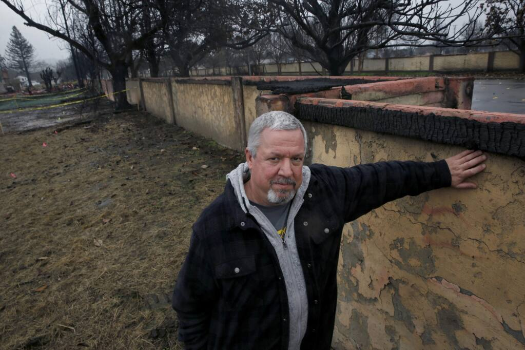Coffey Park resident Kevin Johnson stands next to one of two 1,500-foot-long walls lining Hopper Avenue on Wednesday, Jan. 24, 2018 in Santa Rosa, California. (BETH SCHLANKER/ PD)