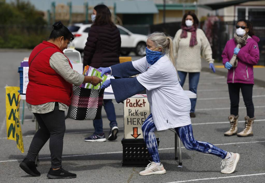 McDowell Elementary School transitional kindergarten teacher Kelly Wood, wearing her husband's bandana over a N95 mask, stretches to put educational material into a bag for a parent outside the school in Petaluma on Monday, April 6, 2020. (BETH SCHLANKER/ The Press Democrat)