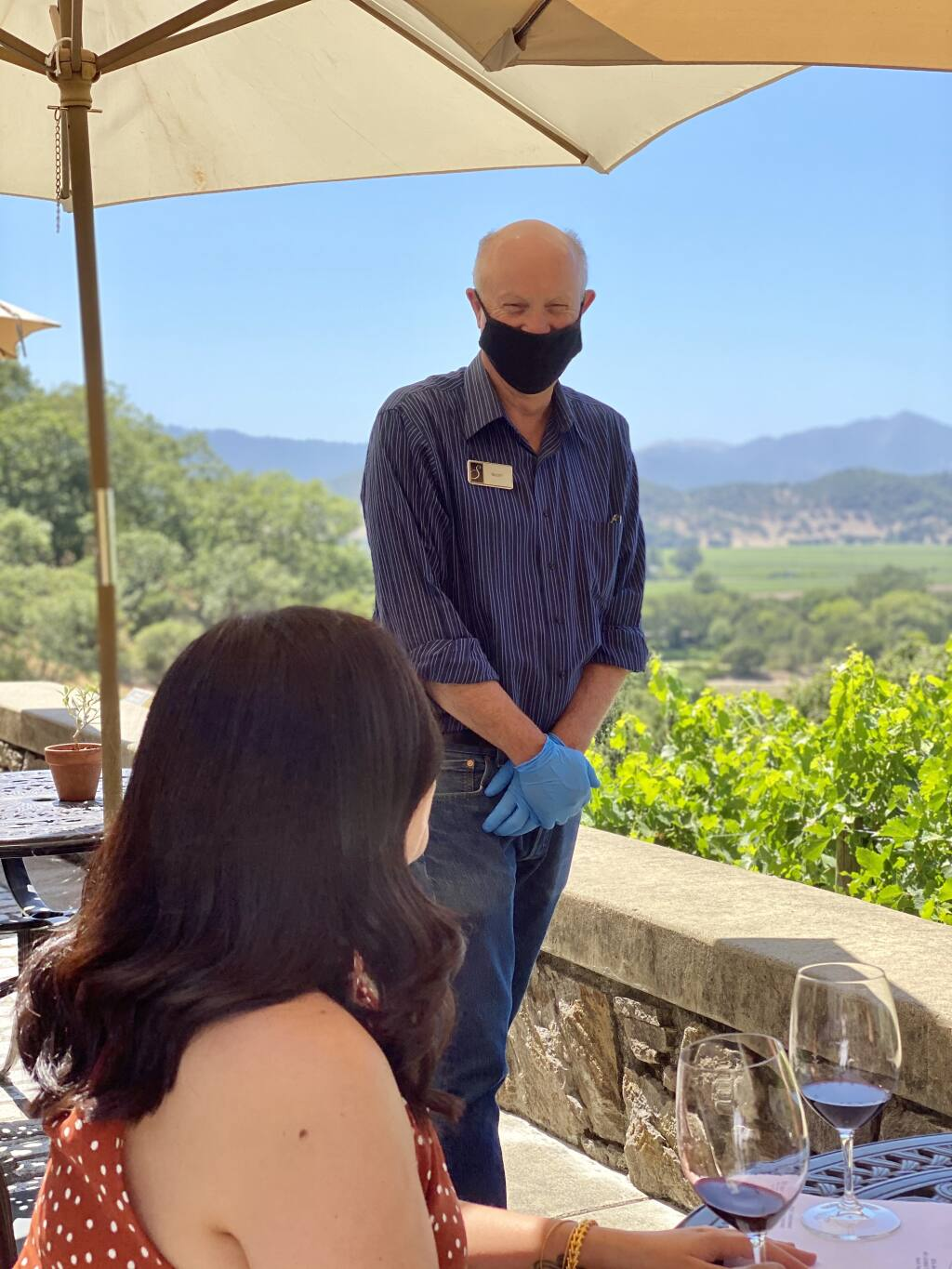 A Silverado Vineyards staff member serves a visitor July 2, 2020, on one of the outdoor terraces overlooking Napa Valley. (courtesy photo)