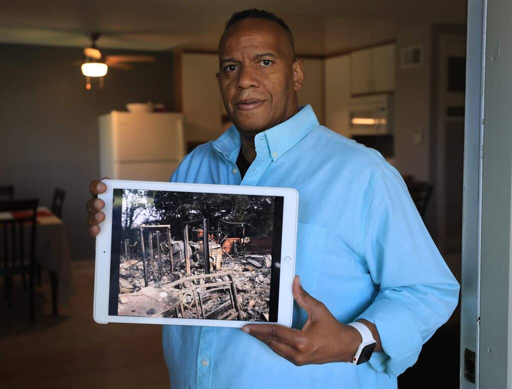 Michael Newton rented a place at Hopper Lane Apartments in Santa Rosa, and was burned from his residence during the Tubbs fire last October, now renting in Rohnert Park/Cotati, Newton shows a picture of his place in which he remembers the amount of doorways that were still standing. Rebuilding Our Community (ROC) aided Newton after physical and financial setbacks left him with little or no income that helped to pay for a security deposit on his new apartment (Kent Porter / The Press Democrat) 2018