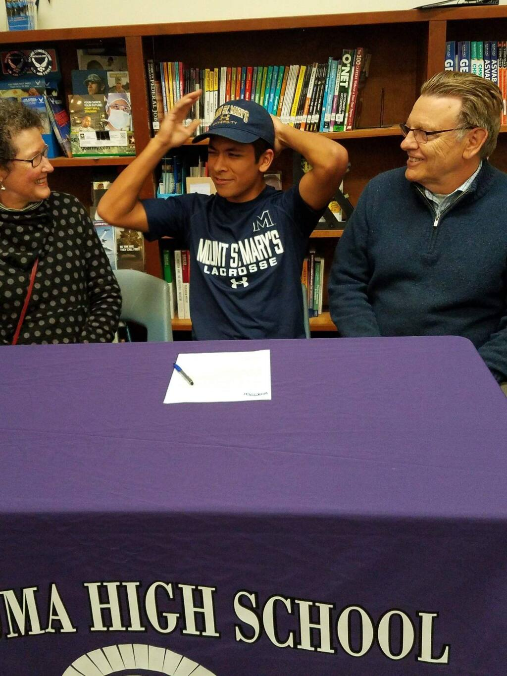 JOHN JACKSON/ARGUS-COURIER STAFFPetaluma High School senior Isaiah Blomgren tries on a Mount St. Mary's cap while proud mother, Peggy, and father, Carl, look on after the athlete signed to play lacrosse for the Maryland university.