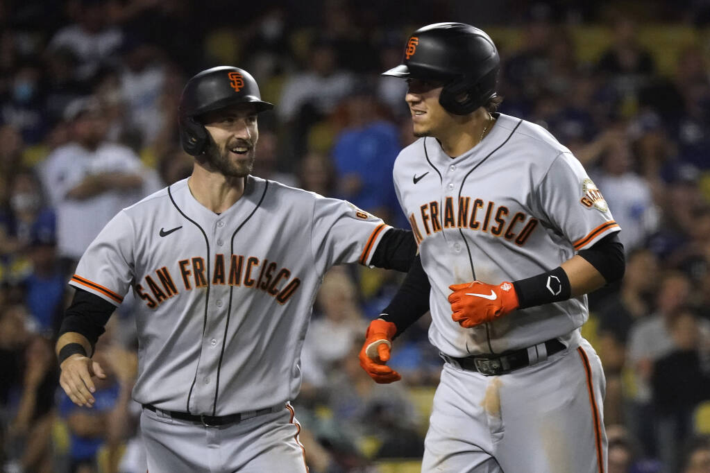 San Francisco Giants' Wilmer Flores, right, celebrates his two-run home run with Steven Duggar during the ninth inning of the team's baseball game against the Los Angeles Dodgers on Wednesday, July 21, 2021, in Los Angeles. (AP Photo/Marcio Jose Sanchez)