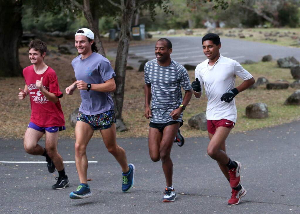 Jonny Vargas, right, a freshman at Santa Rosa Junior College, runs with coach Reesey Byers, P.J. Lynch, and Connor Efstathiu during a workout at Spring Lake Regional Park in Santa Rosa on Tuesday, Oct. 9, 2018. (Beth Schlanker/ The Press Democrat)