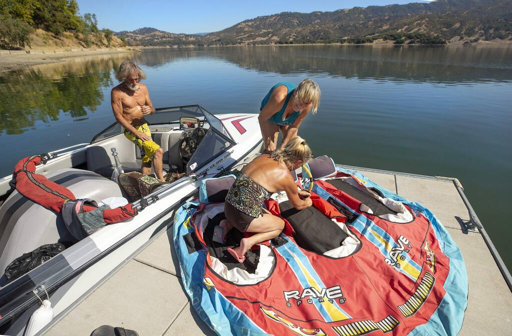 From left, Jimmie McManus, Bobbie Goodyear and Cynthia Clark of Cloverdale prepare for an afternoon boating at Lake Mendocino on Monday. They say this is the most water they've seen in the lake in early fall since they starting camping there 15 years ago. (photo by John Burgess/The Press Democrat)