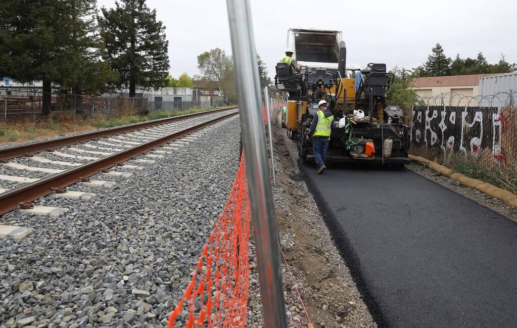 A construction crew paves an asphalt pedestrian pathway alongside the SMART tracks, near Southpoint Boulevard, in Petaluma on Friday, September 27, 2019. (Christopher Chung/ The Press Democrat)