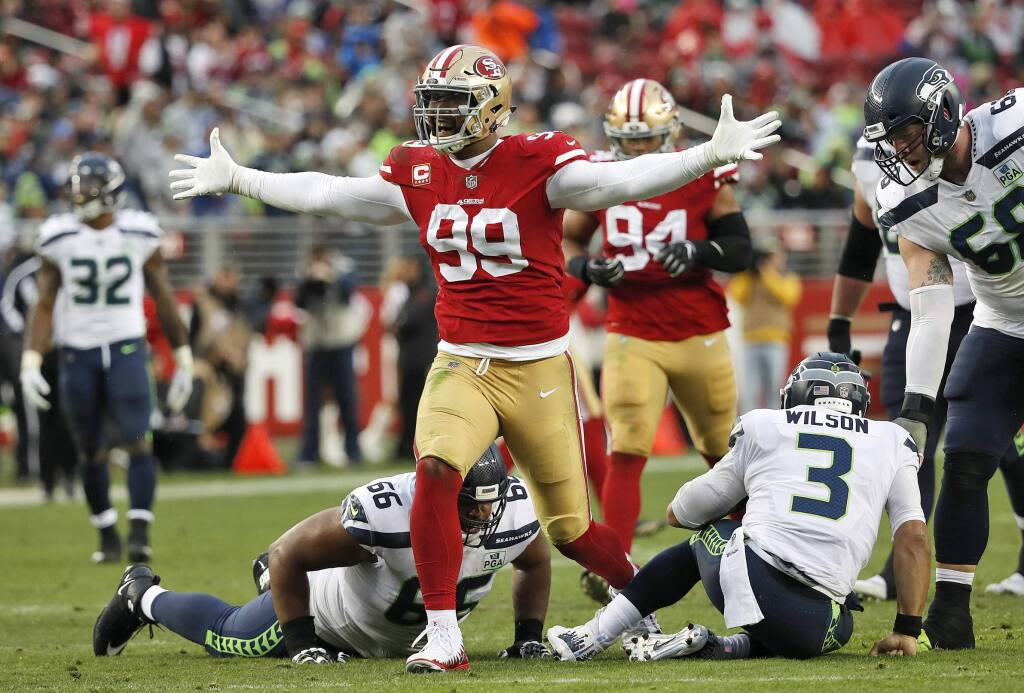 FILE - In this Sunday, Dec. 16, 2018, file photo, San Francisco 49ers defensive end DeForest Buckner (99) celebrates after sacking Seattle Seahawks quarterback Russell Wilson (3) during the second half of an NFL football game in Santa Clara, Calif. Generating pressure on the quarterback has never been a major problem for Buckner since entering the NFL in 2016. Turning that pressure into sacks, however, was missing his first two seasons with the 49ers. (AP Photo/Tony Avelar, File)