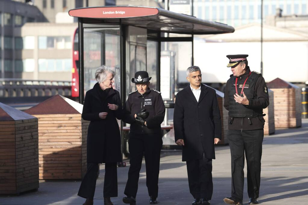 Mayor of London, Sadiq Khan, centre right, Metropolitan Police Commissioner, Cressida Dick, center left, and Commissioner of the City of London Police, Ian Dyson, right, walk across London Bridge in central London, Saturday, Nov. 30, 2019, after an attack on Friday. UK counterterrorism police on Saturday searched for clues into how a man imprisoned for terrorism offenses before his release last year managed to stab several people before being tackled by bystanders and shot dead by officers on London Bridge. Two people were killed and three wounded. (Steve Parsons/PA via AP)