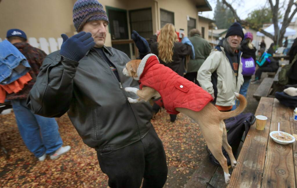 Norman Jensen motions for his dog Ozzie to jump in his arms during a Catholic Charities clothes giveaway in 2014. (KENT PORTER/ PD FILE)