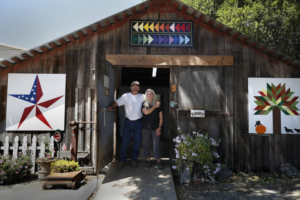 """Rick and Sandy Carroll stand at the door of their barn/studio decorated with a variety of barn quilts, including those with the pattern """"American Star"""", from left, """"Flying Geese"""" and """"Tree of Life"""" in Petaluma on Thursday, June 3, 2021. (Beth Schlanker/The Press Democrat)"""