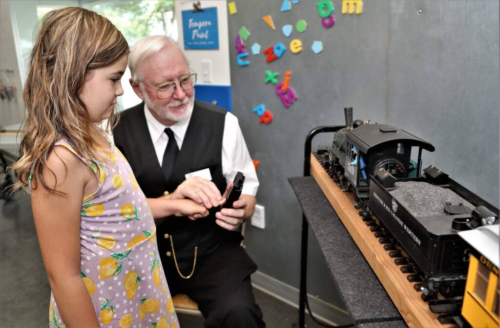 Adalia Petersen, 9, learns how to operate the train with Jim Cunningham at the Great Train Days Celebration put on by the Redwood Empire Garden Railway Society at the Children's Museum of Sonoma County in Santa Rosa on Saturday, July 27, 2019. (WILL BUCQUOY/ FOR THE PD)