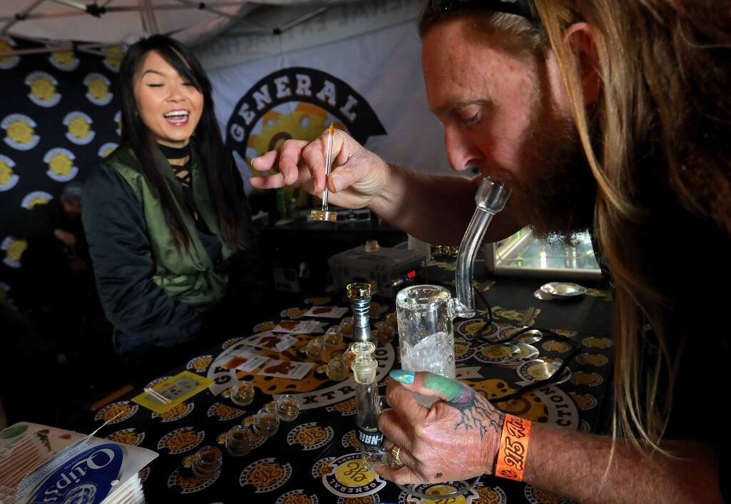 Fergz Farmz tires a dab from Christine Nguyen with General Extractions of Sacramento at the 17th annual Emerald Cup festival at the Sonoma County Fairgrounds on Saturday, December 9, 2017. (photo by John Burgess/The Press Democrat)