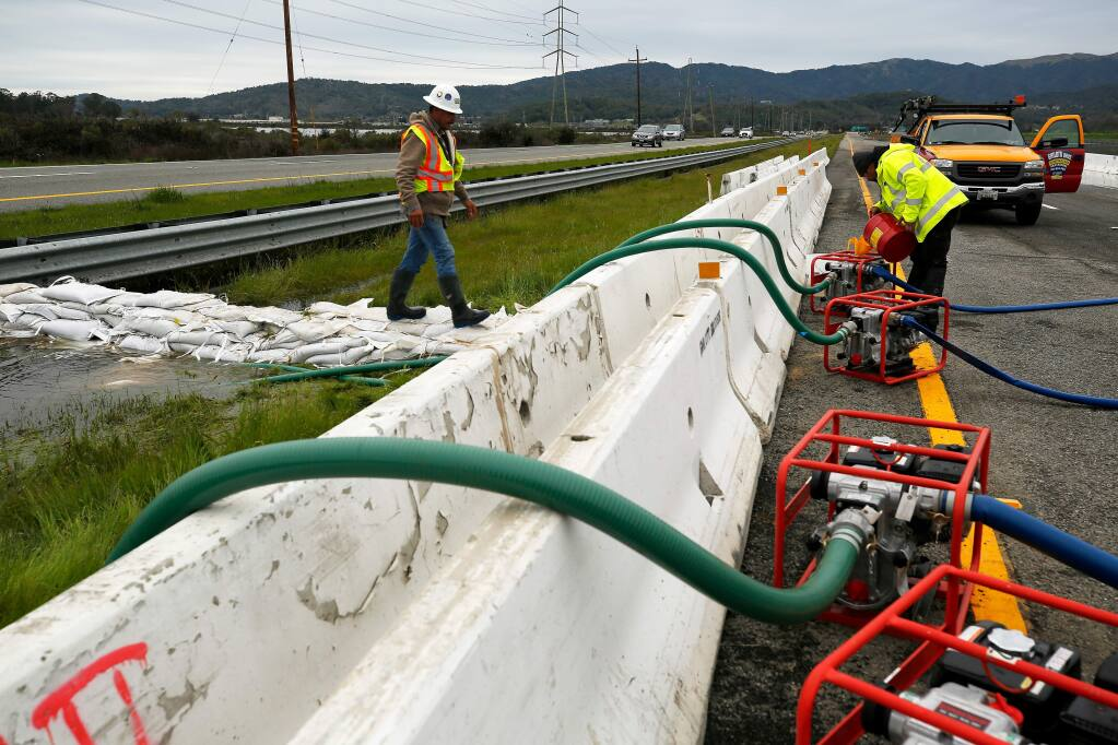Jose Lopez Guzman, left, and Victor Castillo of Ghilotti Brothers construction company check hoses and refuel pumps directing flood water out of the median of Highway 37, where water levels rose after a levee break on Novato Creek, flooding the highway near Novato, California, on Friday, March 1, 2019. (Alvin Jornada / The Press Democrat)