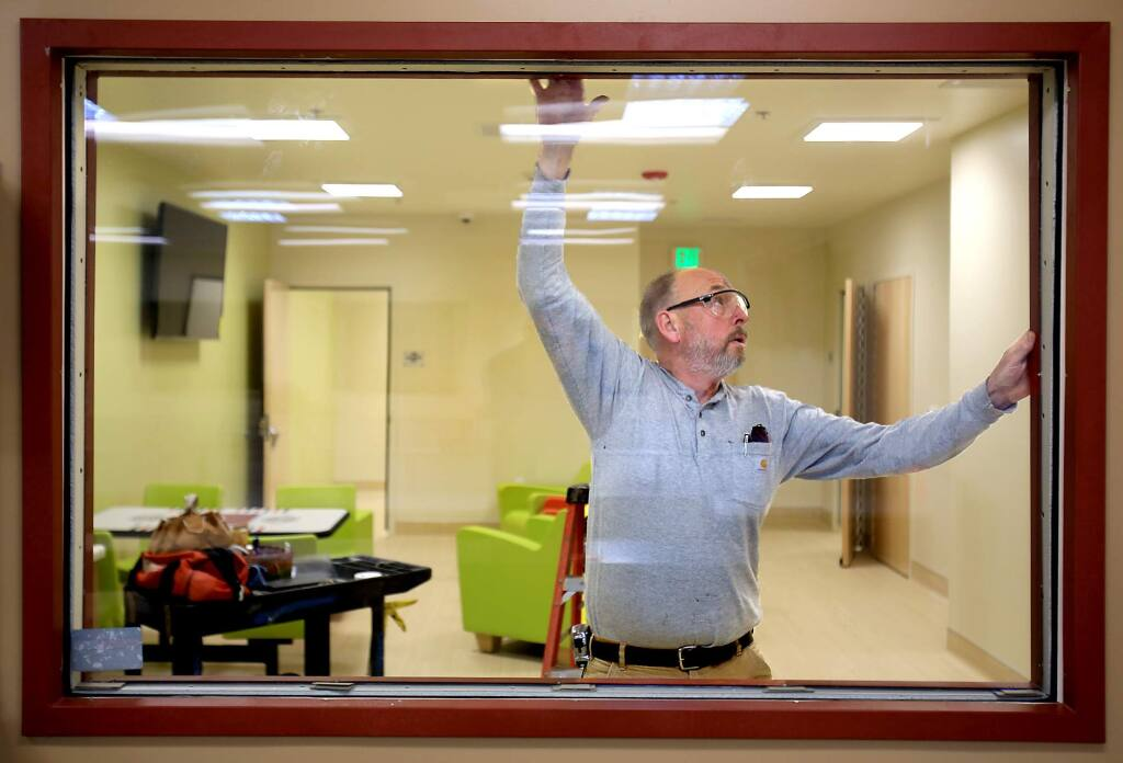 Roger Thoms of Vila Construction in Santa Rosa prepares to fasten a window frame in place at a new mental health facility in Santa Rosa, Wednesday March 2, 2016. (Kent Porter / Press Democrat) 2016