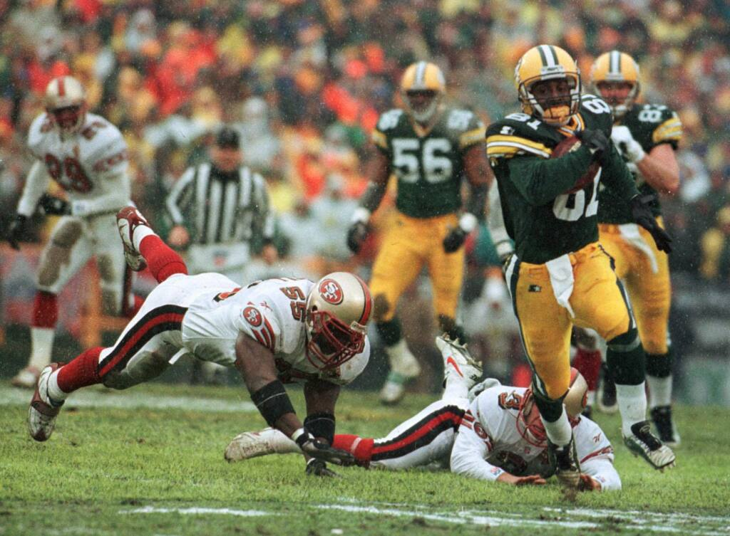 In this Jan. 4, 1997, file photo, the Green Bay Packers' Desmond Howard eludes San Francisco 49ers Kevin Mitchell and Tommy Thompson on the way to a touchdown on a punt return in the first half in Green Bay. (AP Photo/David Boe, File)