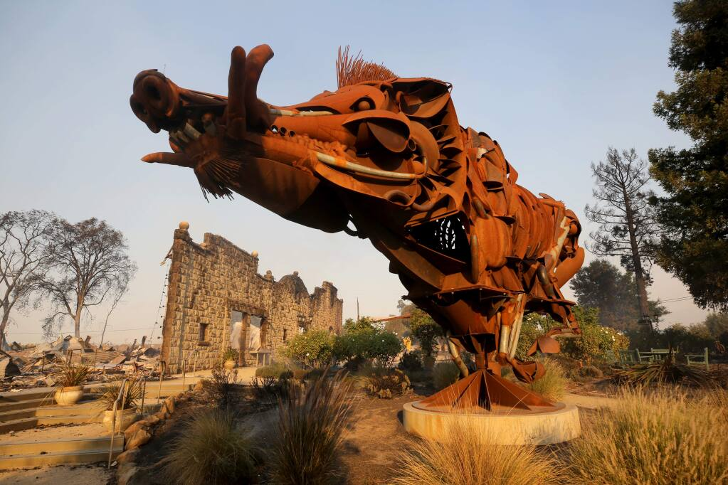 AFTER: A sculpture of a wild boar called 'Lord Snort' stands in front of the charred facade of Soda Rock Winery which burned during the Kincade fire in Healdsburg on Sunday, October 27, 2019. (BETH SCHLANKER/ The Press Democrat)