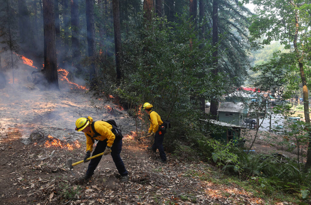Culver City firefighters cut a line to protect a residence from advancing flames along Mill Creek Road near Healdsburg on Tuesday, Aug. 25, 2020.  (Christopher Chung/ The Press Democrat)