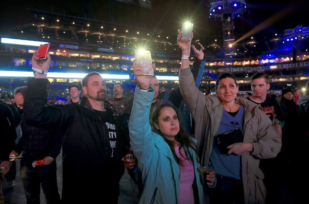Tim and Lori Sarver, left, and Justin and Hollie Tracy lost their homes in Coffey Park in the Tubbs fire, acknowledging their loss by using their phones during Band Together benefit concert for North Bay fire relief in San Francisco, Thursday Nov. 9, 2017. (Kent Porter / The Press Democrat)