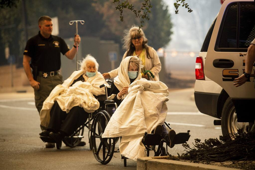 Emergency personnel evacuate patients as the Feather River Hospital burns while the Camp Fire rages through Paradise, Calif., on Thursday, Nov. 8, 2018. Tens of thousands of people fled a fast-moving wildfire Thursday in Northern California, some clutching babies and pets as they abandoned vehicles and struck out on foot ahead of the flames that forced the evacuation of an entire town. (AP Photo/Noah Berger)