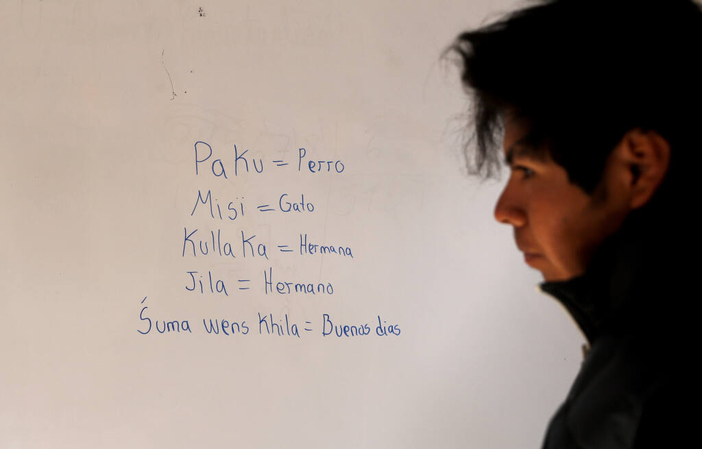 Jose Choque stands next to his work that he wrote on a dry erase board during a Uru language lesson, in a classroom in the Urus del Lago Poopo indigenous community, in Punaca, Bolivia, Monday, May 24, 2021. The last native speakers gradually died and younger generations grew up schooled in Spanish and working in other, more common Indigenous languages, Aymara and Quechua. To save their identities, the Urus are trying to revive their native language. (AP Photo/Juan Karita)