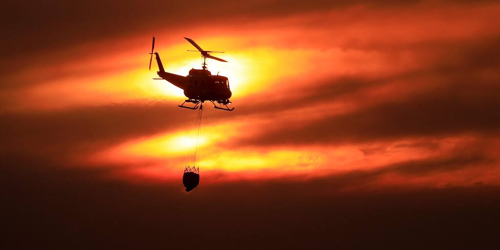 The setting sun is tinged by wildfire smoke and cirrus clouds as the Boggs Mountain Cal Fire Helitack pilot steers the Bell UH-1H Huey helicopter to make a drop in the 500-acre American Fire in Napa/Solano County on Sunday, Oct. 5, 2019 in American Canyon. (Kent Porter / The Press Democrat)