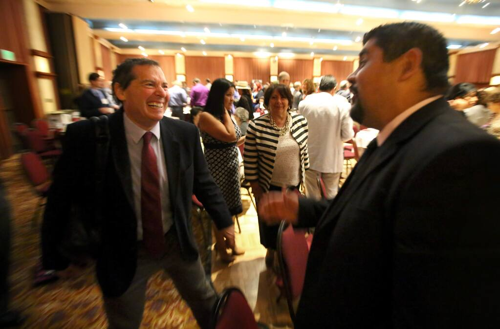 Keynote speaker Dr. David Grusky, professor of sociology at Stanford University, talks with Oscar Chavez, assistant director of human services for Sonoma County, during a break at the Los Cien State of the Latino Community event, in Santa Rosa on Thursday, October 2, 2014. (Christopher Chung/ The Press Democrat)