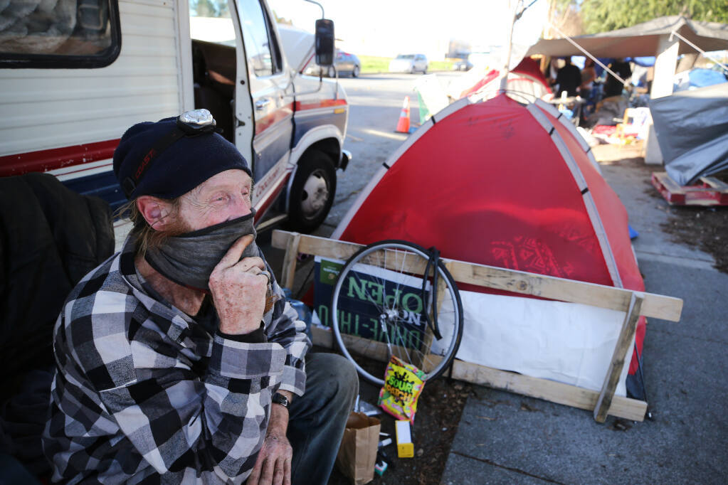 William Barham, who has been homeless for 9 years, sits outside his friend's RV at the homeless encampment on Industrial Dr. in Santa Rosa, Calif., on Monday, January 18, 2021. (BETH SCHLANKER/ The Press Democrat)